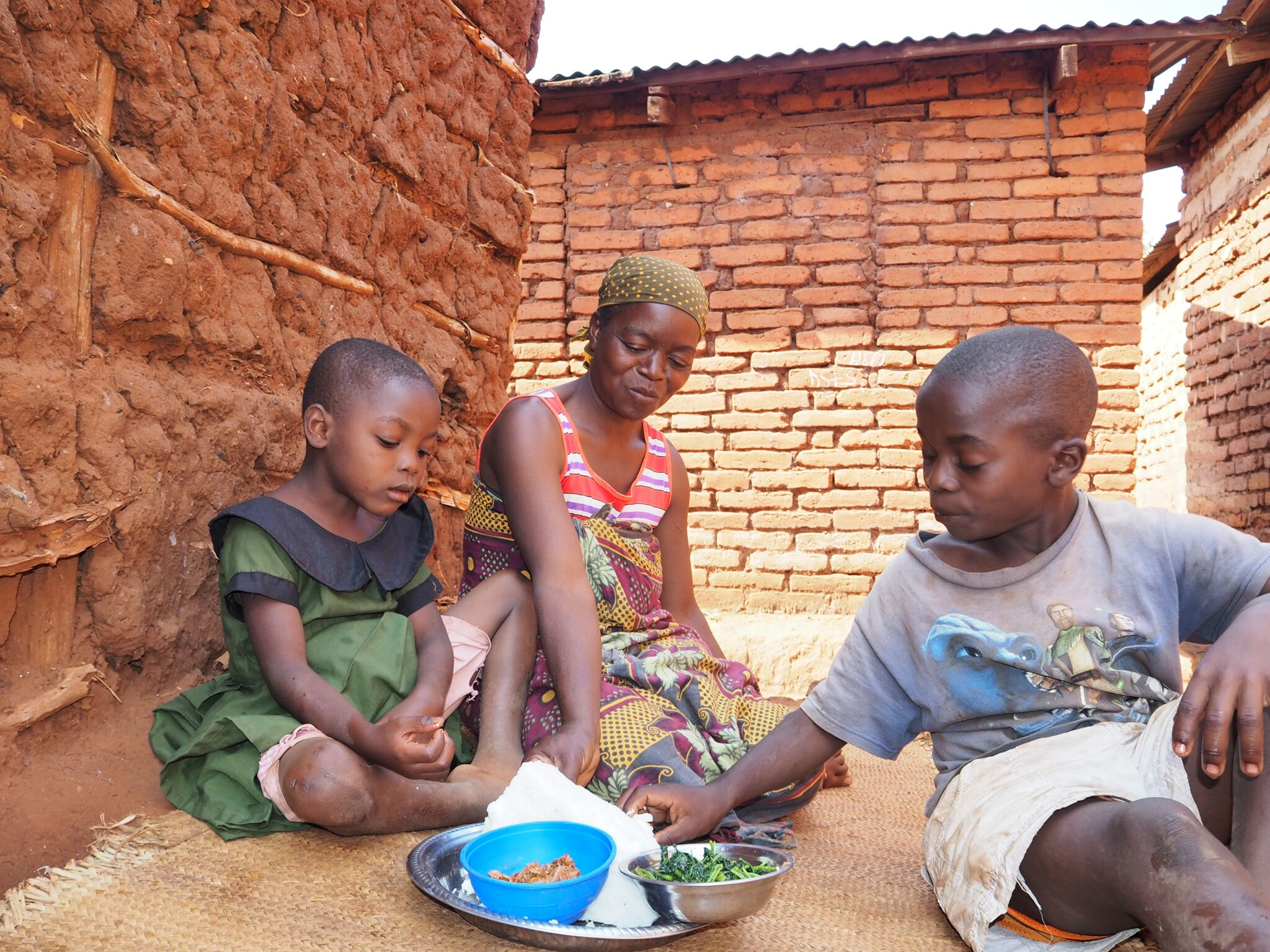 Mama Asha smirking and kids eating ugali preview
